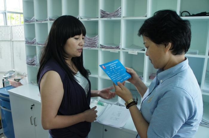 邹蔚秘书长查看金平县妇幼保建院为推动孕产妇免费孕检而制作的记录卡
