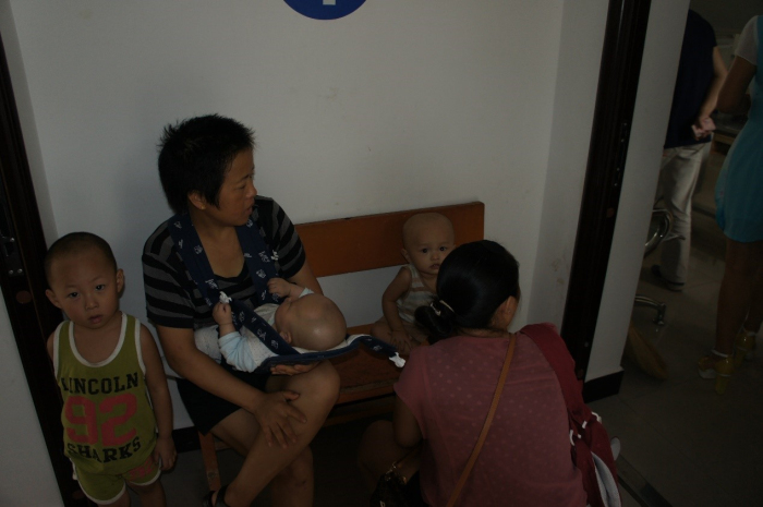 在元阳县妇幼保健院,母亲怀抱婴儿正在等待儿科体检